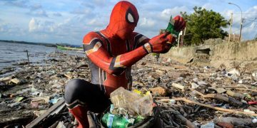 man dresses as spider man to clean trash